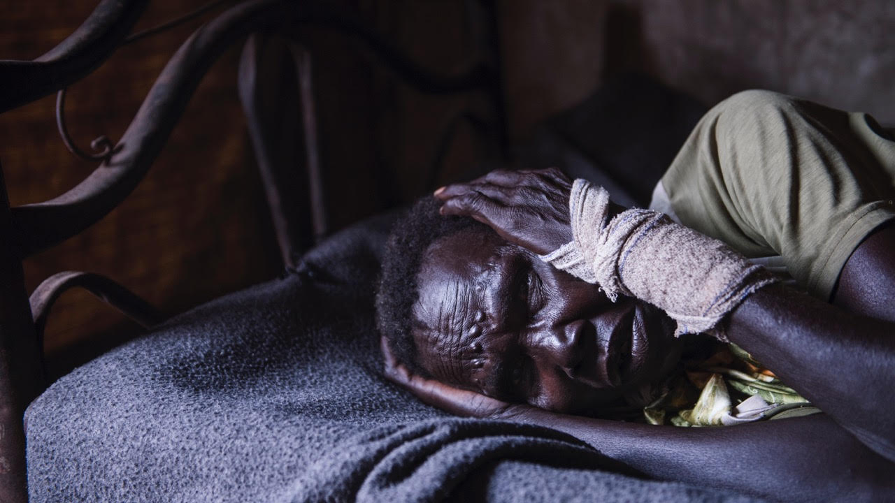 Nyawar Wanth, 70, lays in her bed after recently being raped by a soldier while gathering firewood in northern South Sudan. A human rights team went to monitor her situation and collect her testimony about the recent incident.