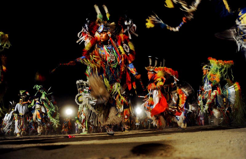 Dancers make their way into the Pow Wow circle during the Grand Entry, Saturday evening at the 98th Annual Shiprock Navajo Fair in Shiprock, N.M. The Navajo Nation's largest traditional gathering began Thursday and ended Sunday.  Events included a rodeo, pow-wow, traditional song & dance, parade and carnival.