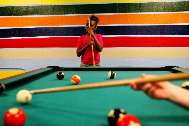Jaida Anderson, 9,  watches as Adrianna York, 8, takes her shot while playing a game of pool during the final day of 'Spring Fever{quote} spring break camp at Lincoln Park Community Center.photo by: Amanda Voisard
