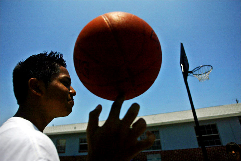 Jose Martinez, 14, spins the ball on his finger while playing basketball on Tuesday afternnoon at his friend, Alejandro Acosta's home.photo by: Amanda Voisard