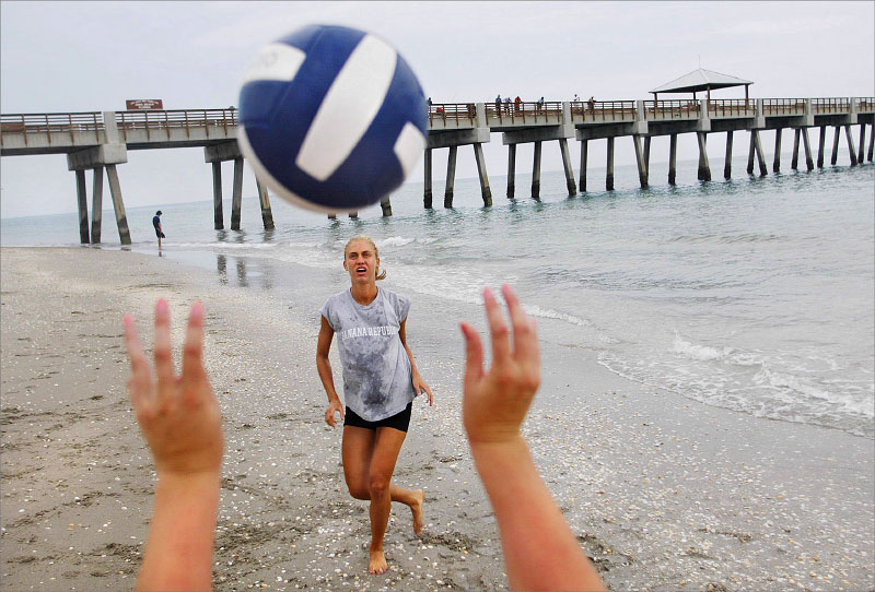 Kelly Murray waits for the return  while playing volley ball with Christina Morrow, (hands), near the Juno Beach pier.photo by: Amanda Voisard