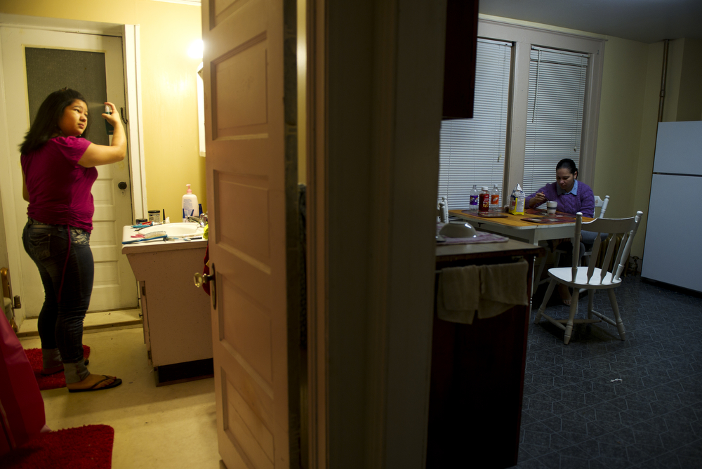 Daniela Valesquez, 14, gets ready for school as her mother, Silvia Cruz   rests before heading to work, Friday morning.