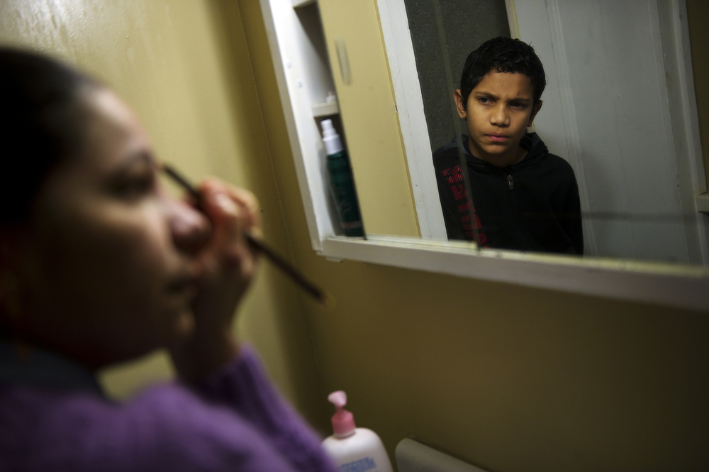 Silvia Cruz prepares for the day as her son, Camilo Velasquez, 12, waits for her.