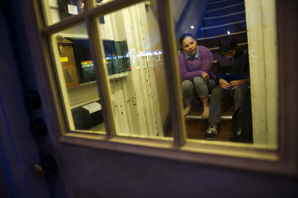 Silvia Cruz waits with her son, Camilo Velasquez, 12, for the bus to arrive early Friday morning in the stairwell of their apartment building.