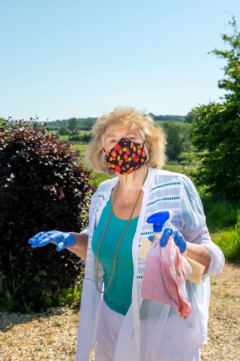 Sarah Wiseman with mask and cleaning products about to drive the car, Thackeston, North Cadbury, Somerset, England