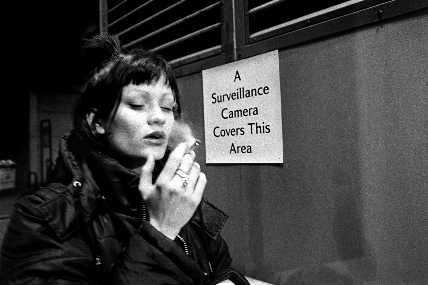 A young woman smokes a joint outside of a club in London. Winter 1998