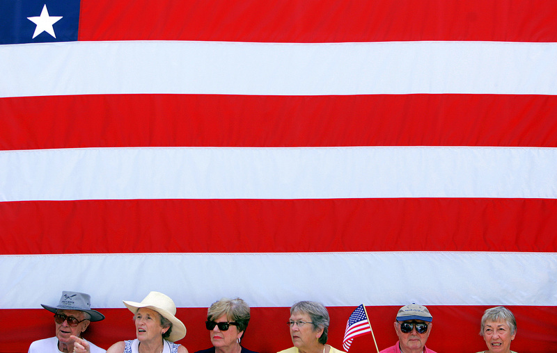 Clinton supporters sit beneath a flag as they wait at a Hillary Clinton campaign event with her husband former President Bill Clinton at the University of Iowa in Iowa City, Iowa, on Tuesday, July 3, 2007. (Photo by Chris Schneider)