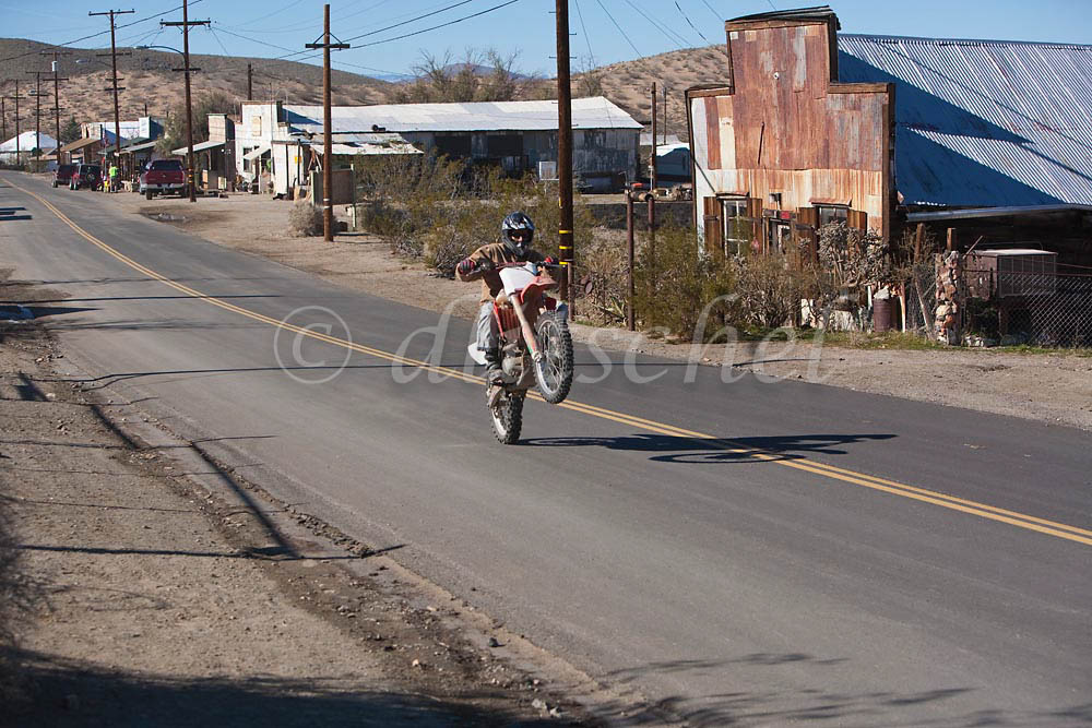 A dirt bike does a wheelie down main street in Randsburg California, a {quote}living ghost town{quote} that attracts off road and motocross motorcyclists during the cooler winter weather in this Mojave Desert location. To purchase this image, please go to my stock agency.
