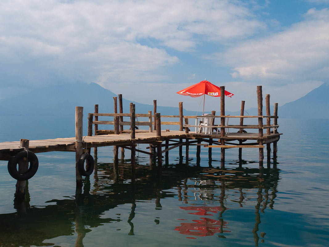 A bright red umbrella on the end of a wooden pier stands out against the blue sky and reflects in the waters of Lake Atitlan, Guatemala.