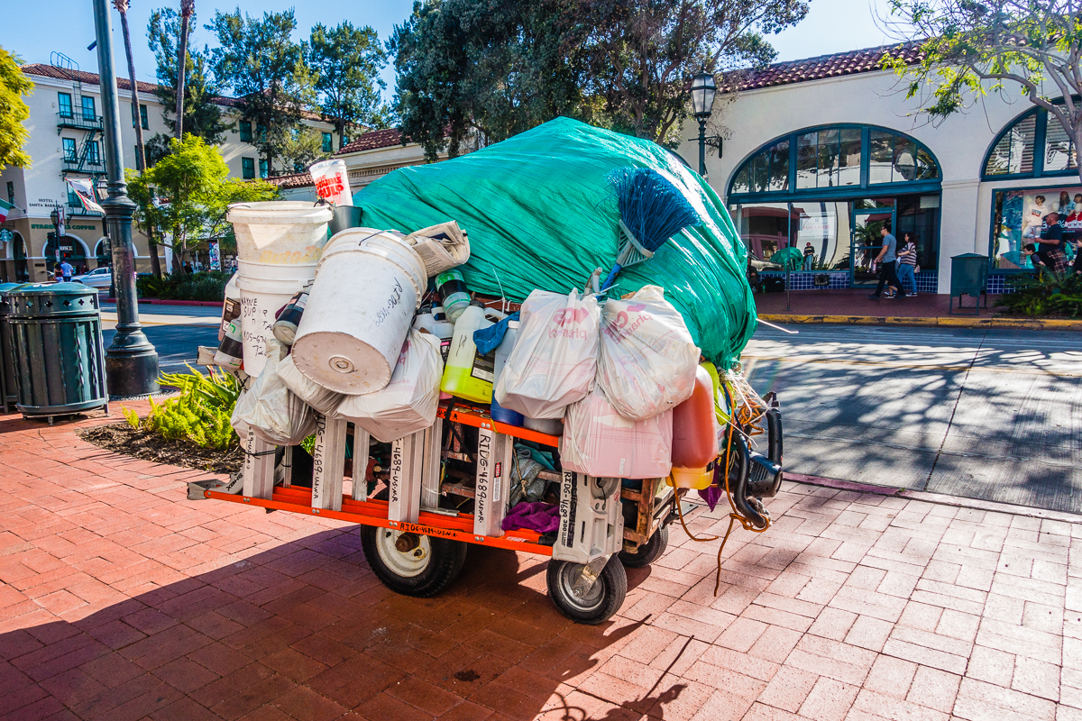Homeless person's belongings on an overloaded cart on the sidewalk in Santa Barbara, California.