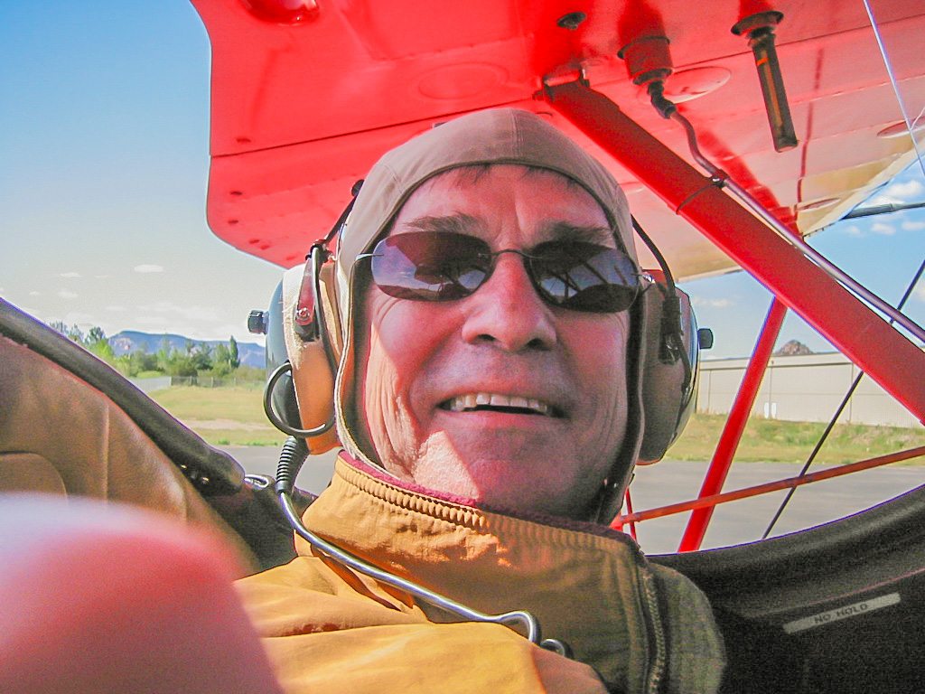 Selfie in red biplane wearing old style aviator head gear in Sedona, Arizona.