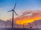 A wind farm outside of Palm Springs, California during a colorful sunset. A wind turbine is a device that converts kinetic energy from the wind into electrical power. The term appears to have migrated from parallel hydroelectric technology (rotary propeller). The technical description for this type of machine is an aerofoil-powered generator.The result of over a millennium of windmill development and modern engineering, today's wind turbines are manufactured in a wide range of vertical and horizontal axis types. The smallest turbines are used for applications such as battery charging for auxiliary power for boats or caravans or to power traffic warning signs. Slightly larger turbines can be used for making contributions to a domestic power supply while selling unused power back to the utility supplier via the electrical grid. Arrays of large turbines, known as wind farms, are becoming an increasingly important source of renewable energy and are used by many countries as part of a strategy to reduce their reliance on fossil fuels.