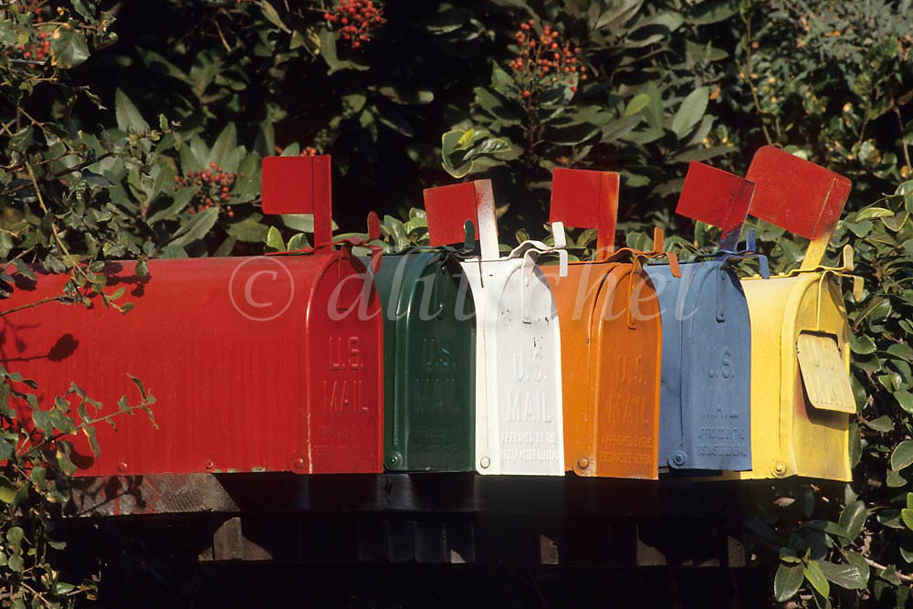 Colorful mailboxes line up in a row displaying their flags in Santa Barbara, California. To purchase this image, please go to my stock agency click here.