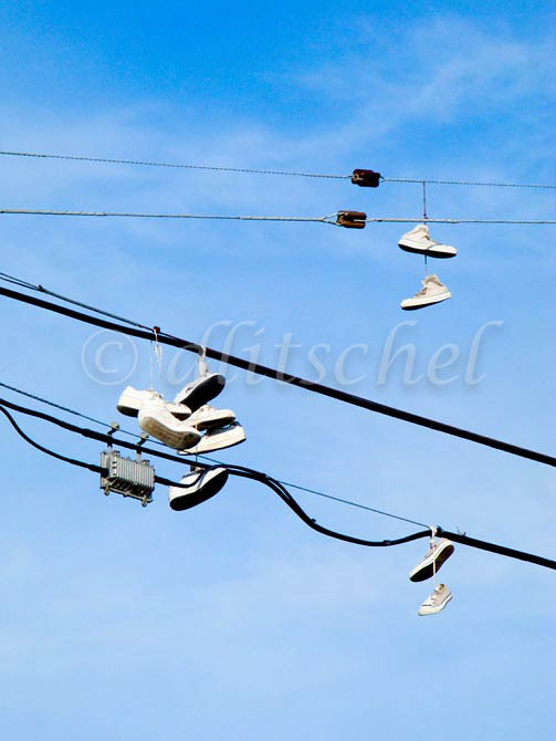 Several pairs of sneakers dangle from power lines in Santa Barbara, California. To purchase this image, please go to my stock agency click here.