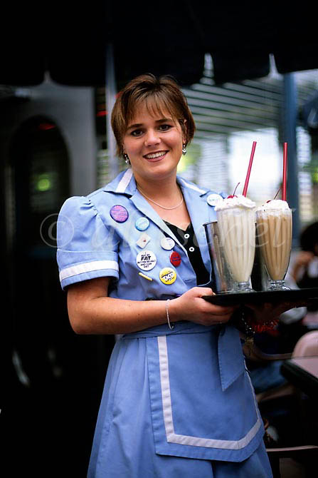A restaurant waitress in San Diego, California carries a tray full of milk shakes. To purchase this image, please go to my stock agency.
