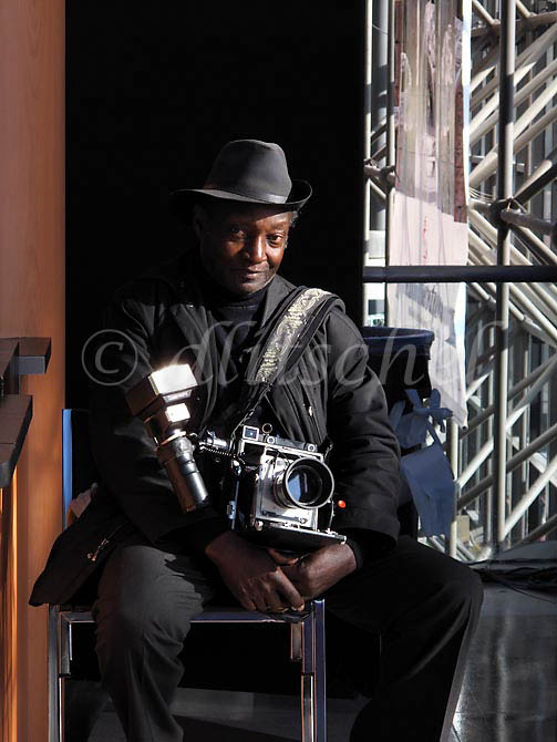 An old time African American New York City photographer displays his 4x5 press camera at the Javitts Center, To purchase this image, please go to my stock agency.