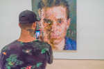Man looking at Chuck Close Painting