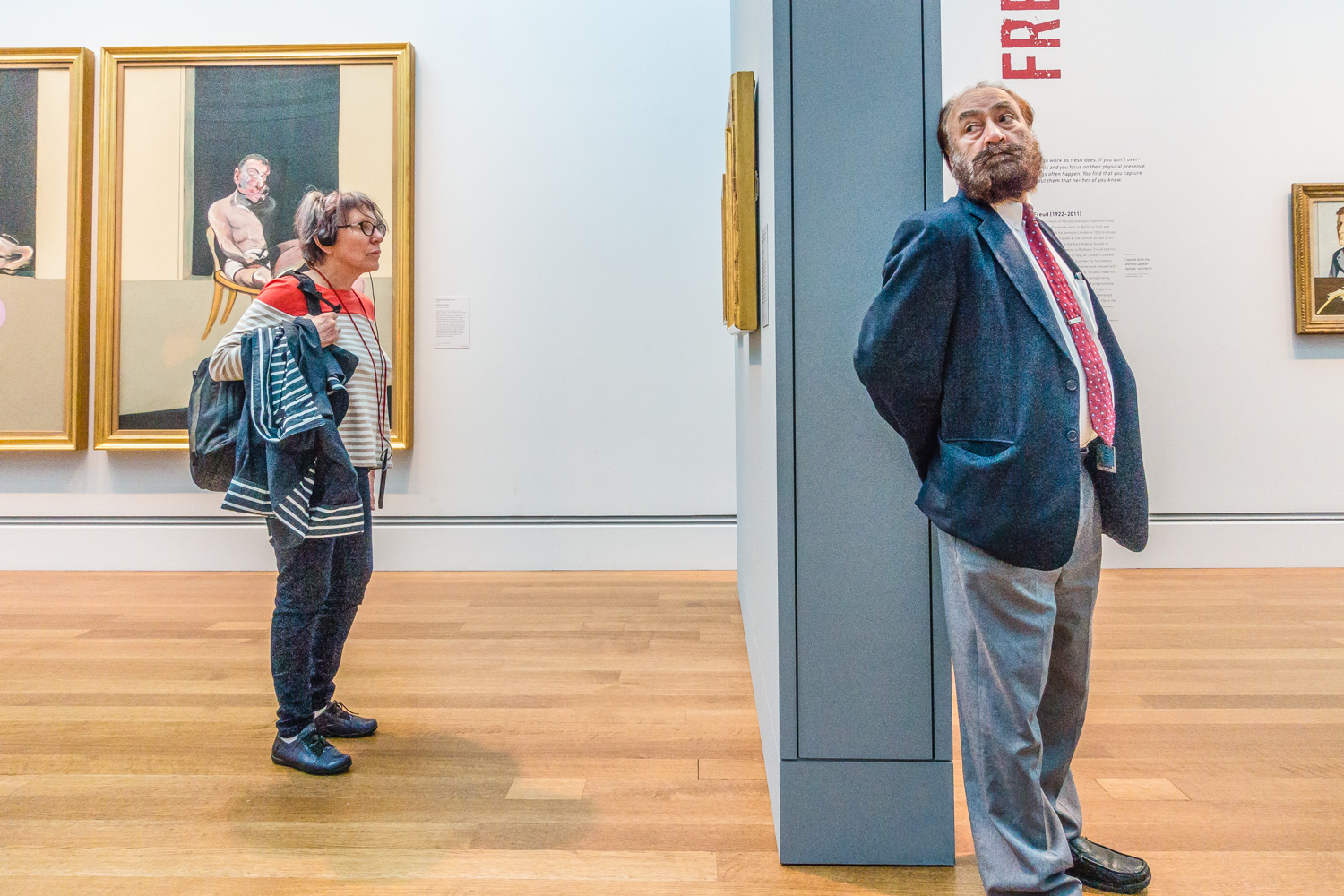 An older female with her audio tour head phones stands in front of a Francis Bacon triptych in a museum  exhibition of his work while a wall separates her from a museum guard leaning against the end of the wall looking away. Francis Bacon (28 October 1909 – 28 April 1992) was an Irish-born British figurative painter known for his bold, grotesque, emotionally charged and raw imagery.His painterly abstracted figures are typically isolated in glass or steel geometrical cages, set against flat, nondescript backgrounds. Bacon took up painting in his early 20s but worked sporadically and uncertainly until his mid-30s. He drifted as a highly complex bon vivant, homosexual, gambler and interior decorator and designer of furniture, rugs and bathroom tiles. He later admitted that his artistic career was delayed because he spent too long looking for subject matter that could sustain his interest.