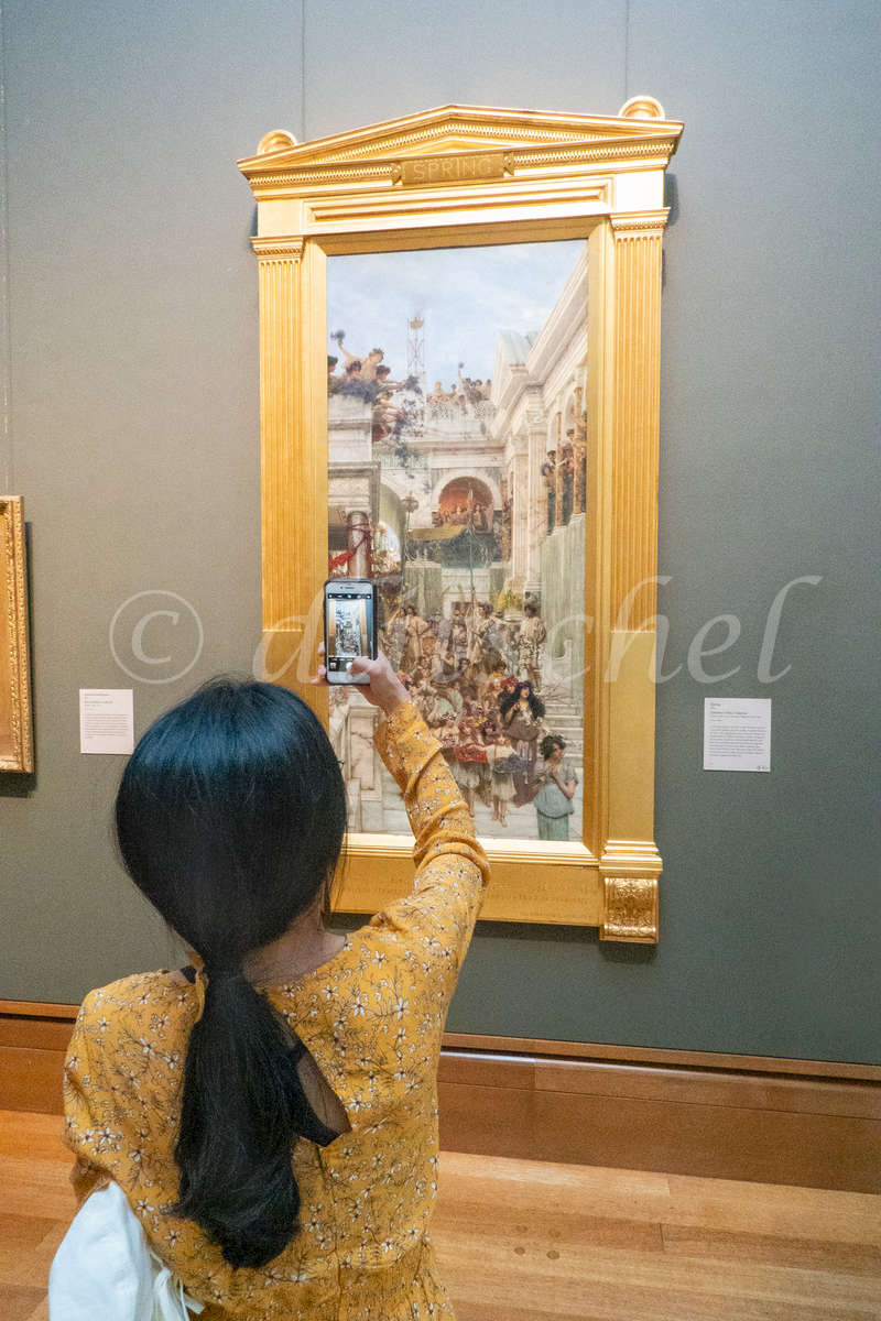Female photographing painting by Lawrence Alma-Tadema in museum.