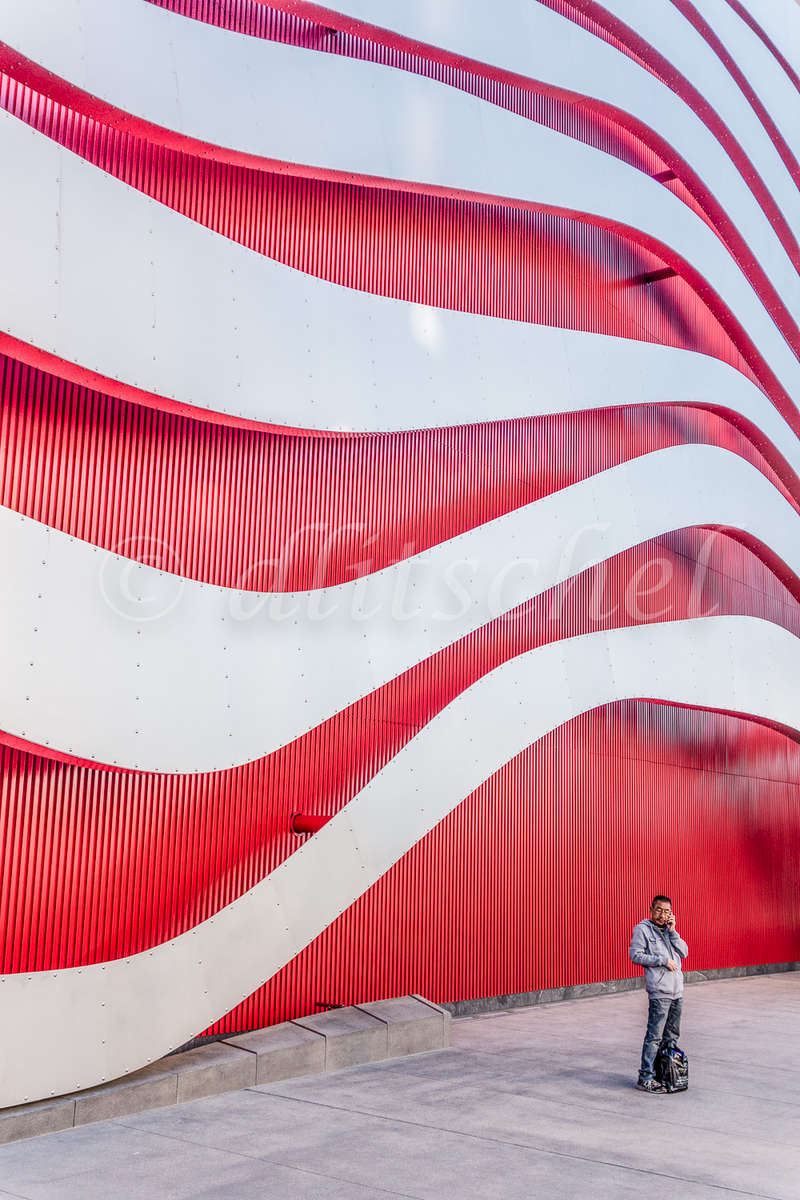 A person is dwarfed by the exterior of the contemporary architecture of the Petersen Automotive Museum in Los Angeles.