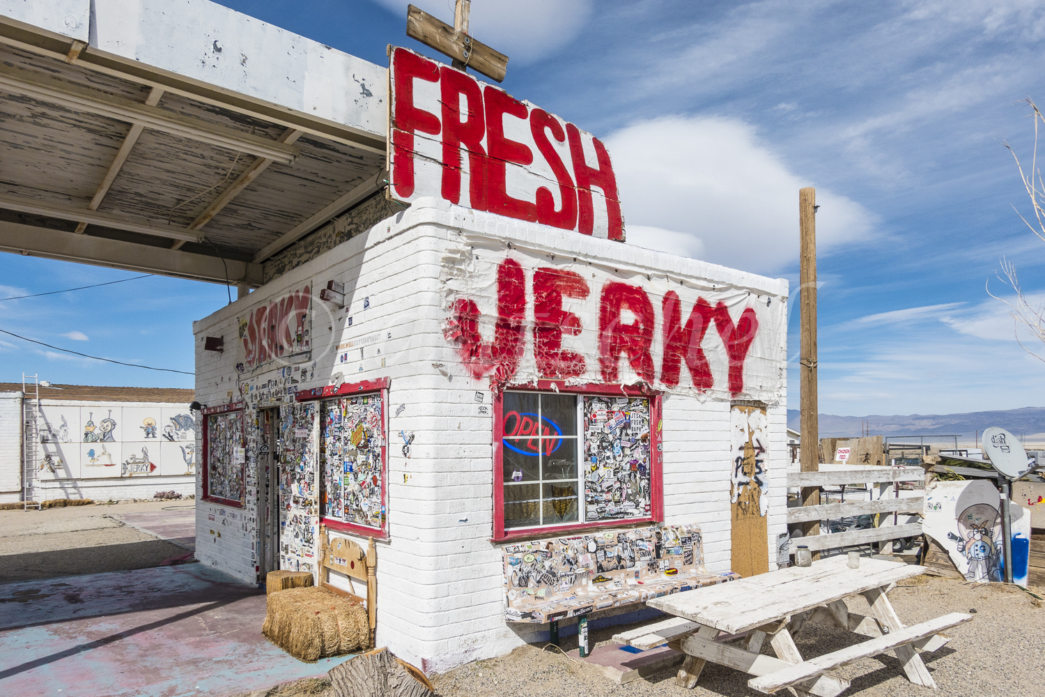 A small older white brick building along California highway 395 in the Eastern Sierras advertises the jerky it sells in huge red letters painted on the side of the building and on a sign atop the building.