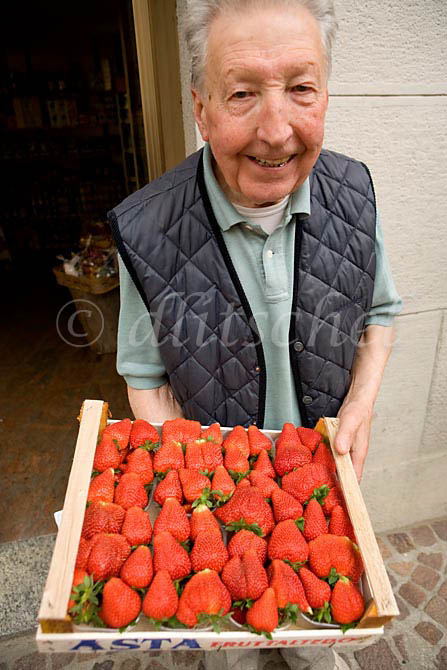 An Italian grocer proudly displays a tray of his strawberries in Brunate, Italy. To purchase this image, please go to my stock agency click here.