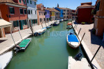 A canal is lined with small boats and colorful houses on the Italian island of Burano off the coast of Venice, Italy. To purchase this image, please go to my stock agency click here.