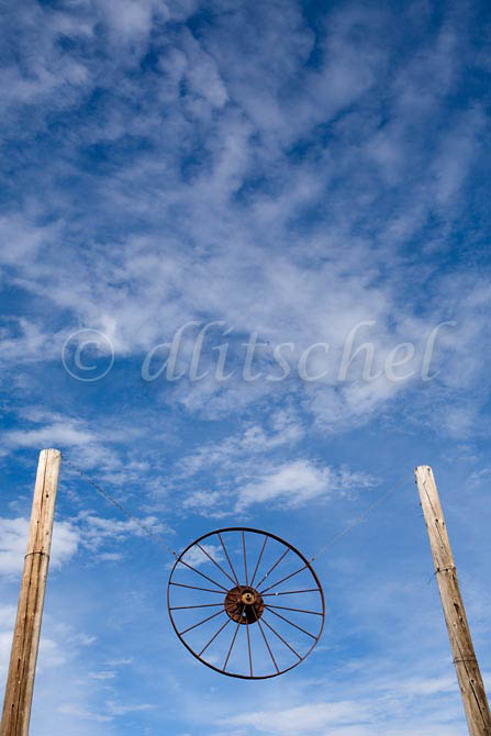 A traditional spoked wagon wheel from a western wagon is suspended between two poles above a ranch in the Santa Ynez Valleyof California. To purchase this image, please go to my stock agency click here.