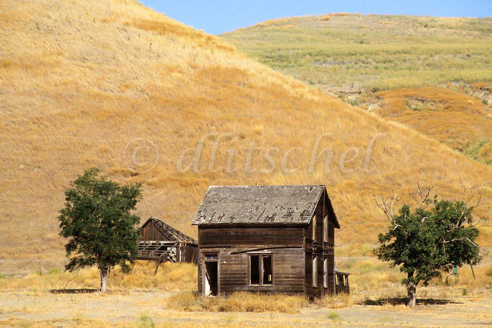 Abandoned farm buildings sit against dry golden hills in the Central Valley of California. To purchase this image, please go to my stock agency click here.