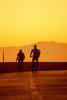 Two bicycle riders are silhouetted against mountains during a golden sunset in Santa Monica, California. To purchase this image, please go to my stock agency.