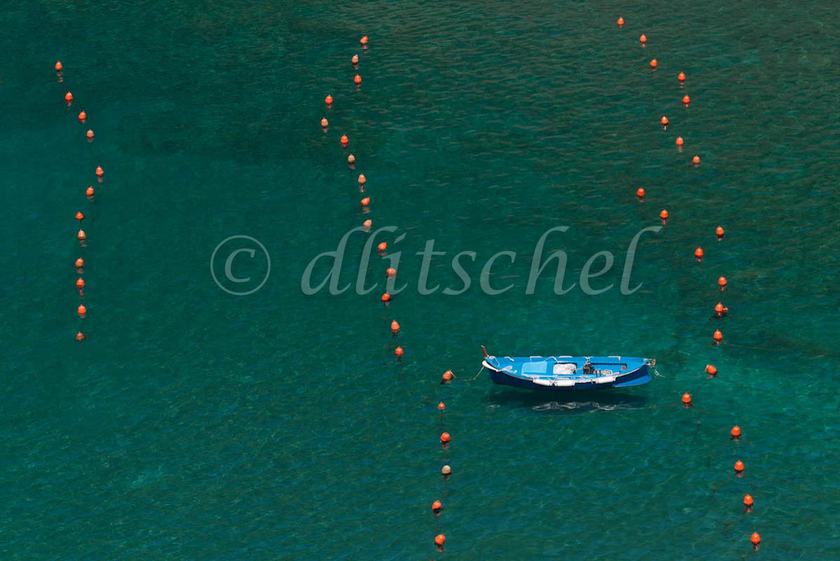 Blue boat in green water of the harbor at Vernazza, Cinque Terre, Italy, with lines of orange buoys on either side.