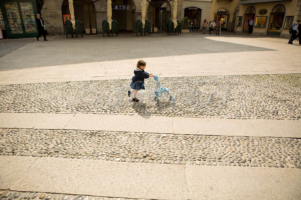 An Italian toddler pushes a baby stroller in the Lake Como city of Como Italy. To purchase this image, please go to my stock agency click here.