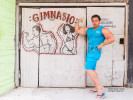 A well built male Cuban body builder poses with muscles flexed in front of his gym where he works out. Behind him on the wall are two drawings of body builders, one male and one female.
