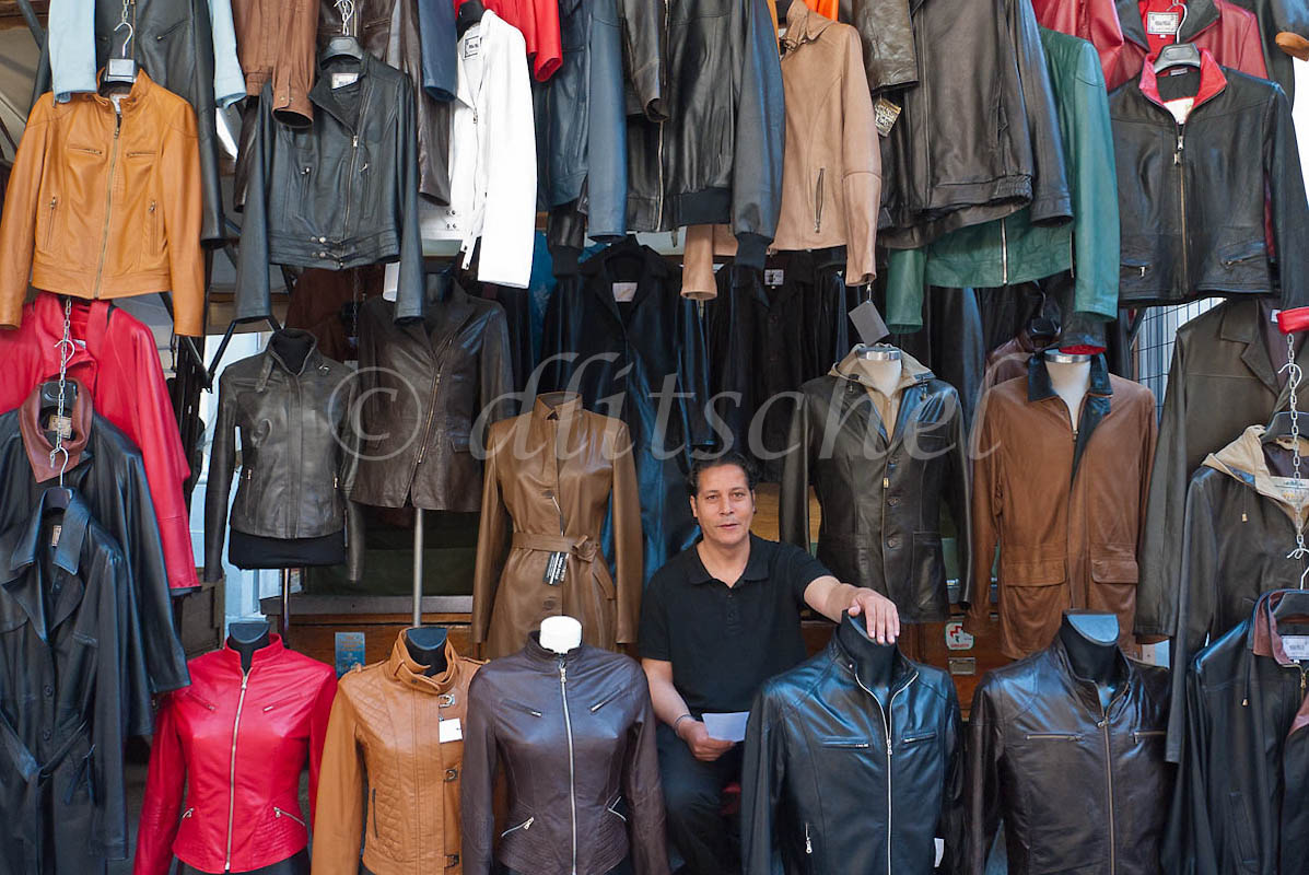 A leather salesman stares ahead as he sits down among his leather jackets and coats for sale in his stall outside the central market in Florence, Italy.