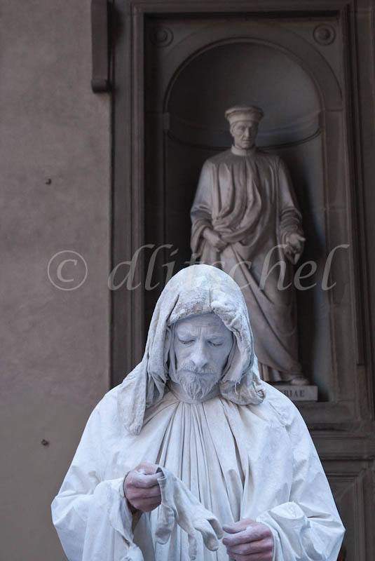 A street performer dressed in all white and white face mimics the dress of the statue from Renaissance times in front of the Uffitzi Gallery in Florence, Italy.