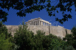 A distant view framed by trees and shrubbery of the Parthenon located on the Acropolis. To purchase this image, please go to my stock agency click here.