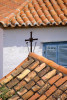 A detail of a Greek church showing tile roof  and cross on the island of Hydra, one of the Saronic Islands, located in the Aegean Sea between the Saronic Gulf and the Argolic Gulf. To purchase this image, please go to my stock agency click here.