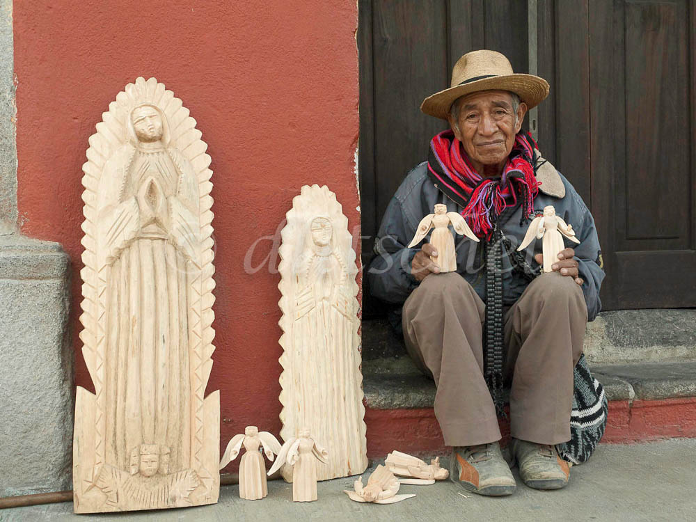 A seasoned wood carver making wooden statues for sale to tourists sits in a doorway in the early hours of the morning.