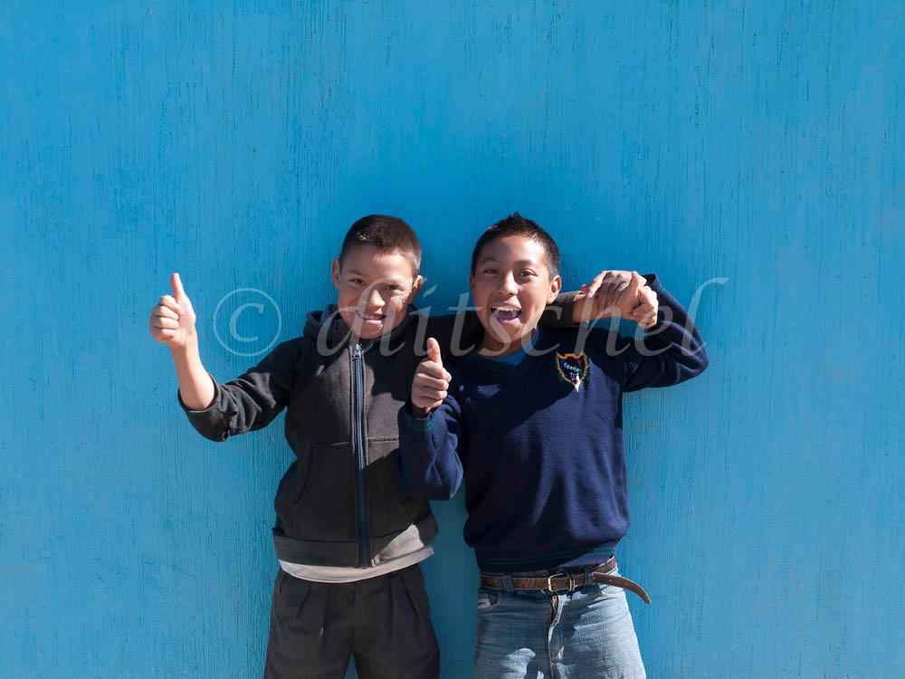 Two elementary school boys ham it up for the camera with a burst of enthusiam.