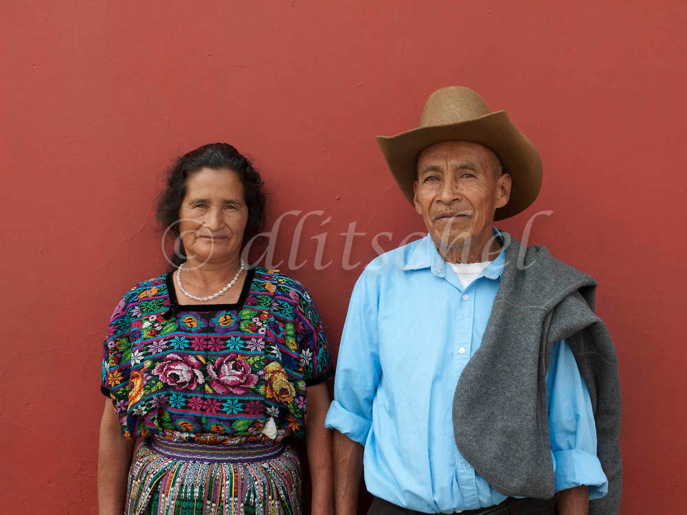 An older married couple pose against a deep terra cotta wall in their traditional dress, in Antigua, Guatemala.