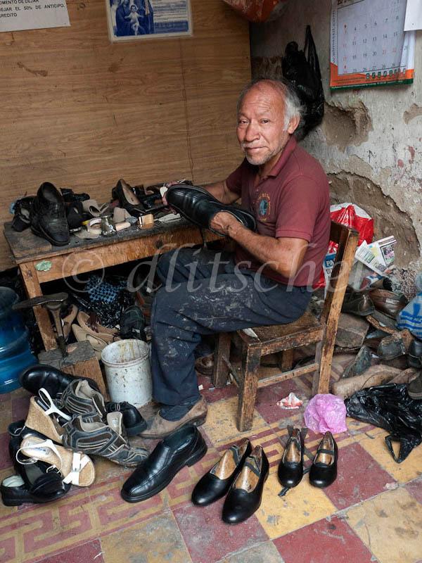 A shoemaker working in his shoe repair shop in Antigua, Guatemala.