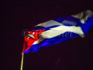 The Cuban flag flies at night lit against the black sky.