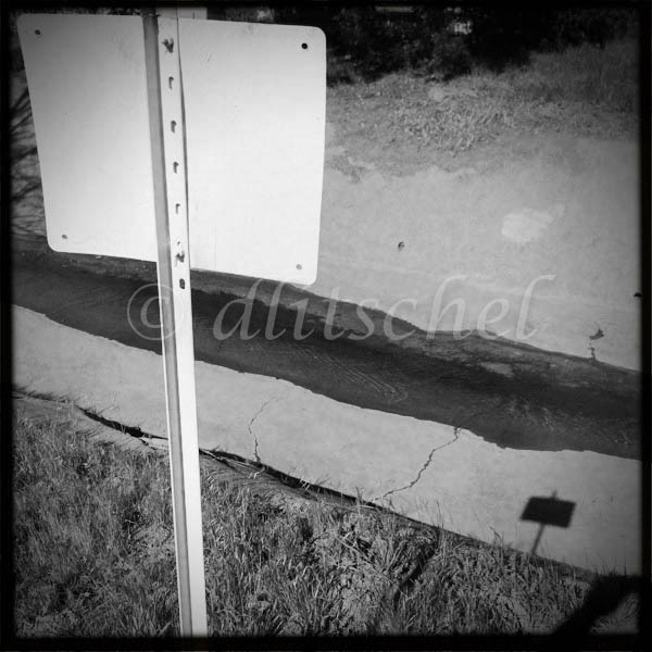 Abstract image of rear of sign with no lettering its cast shadow.