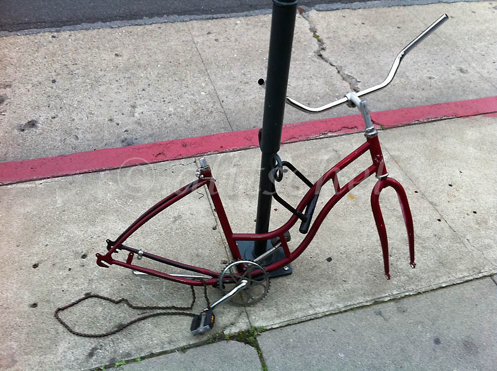 Red bicycle missing wheels, seat and other parts chained to pole in downtown Santa Barbara, CA