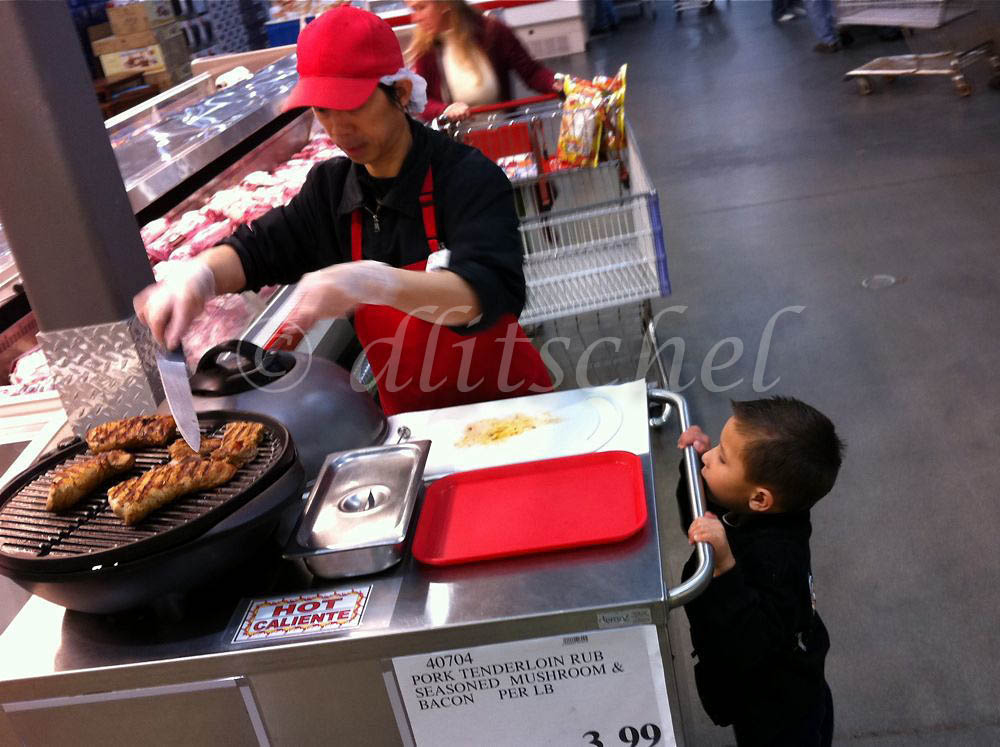 A young hispanic boy holds himself up by the rail of a serving cart to see the pork tenderloin being cut up into samples for customers to try.