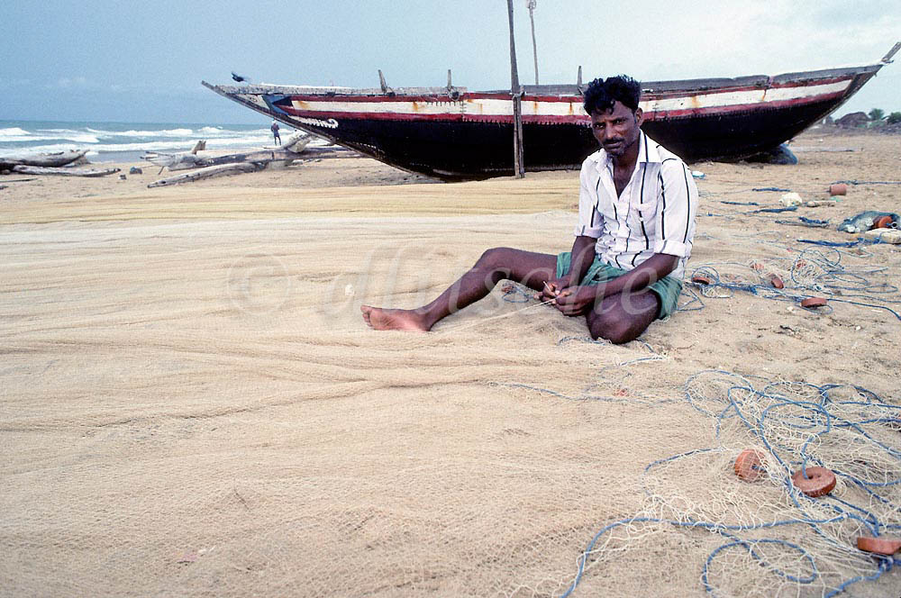 An Indiian fisherman in  Mamallapuram, India ,in the state of Tamil Nadu, sits by his boat and mends his fishing nets. To purchase this image, please go to my stock agency click here.