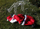 A deflated inflatable Santa Claus lies on the ground next to one of his (electronic) reindeer, aparently dead.
