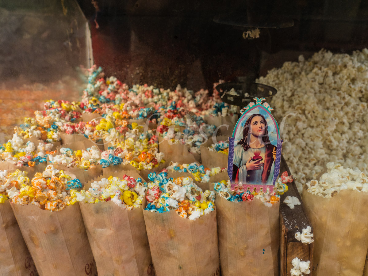 Printed paper Jesus in bag of colored popcorn along with other bags of colored popcorn in a popcorn vendor's cart along a street in Capiata, Paraguay.