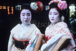 Two Maiko photographed as they walk at dusk in the former Imperial city of Kyoto in the central part of the island of Honshū, Japan. To purchase this image, please go to my stock agency.