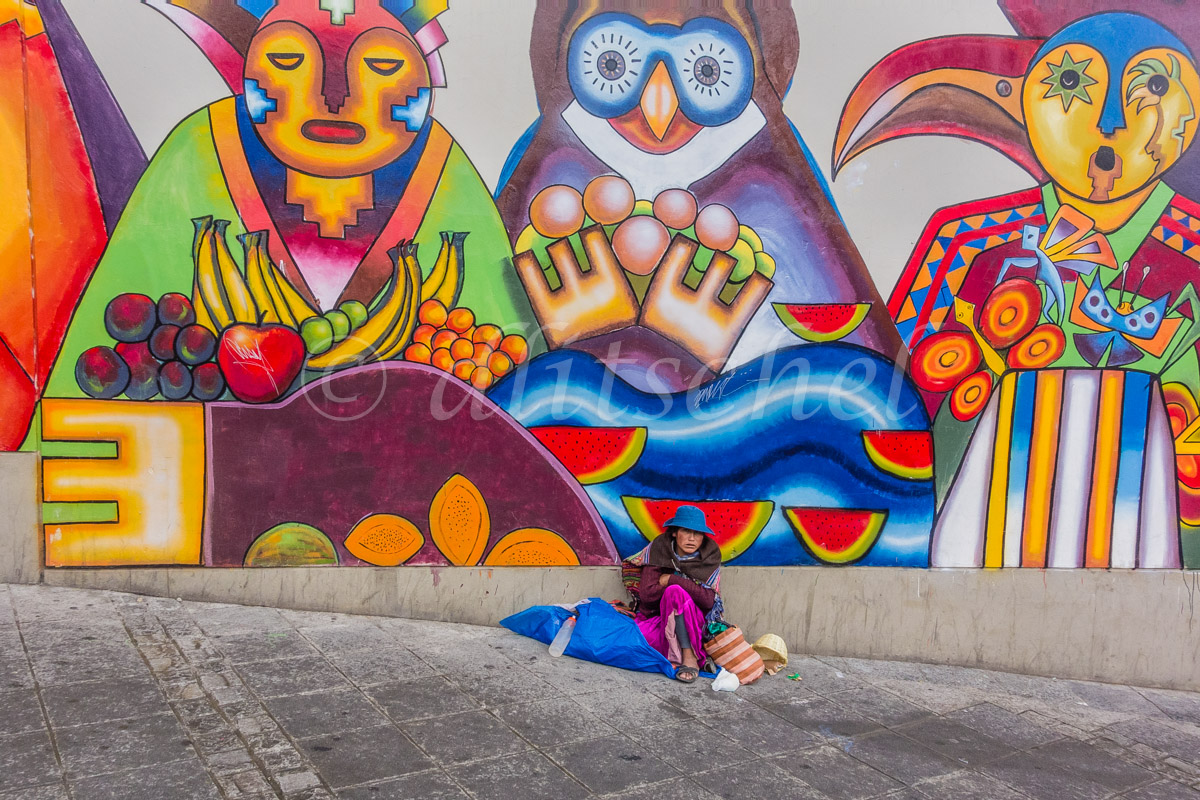Woman seated by colorful mural, La Paz, Bolivia.